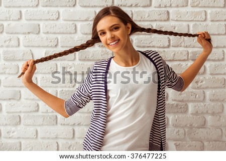 Cute teenage girl in casual clothes playing with her braids, looking in camera and smiling, standing against white brick wall
