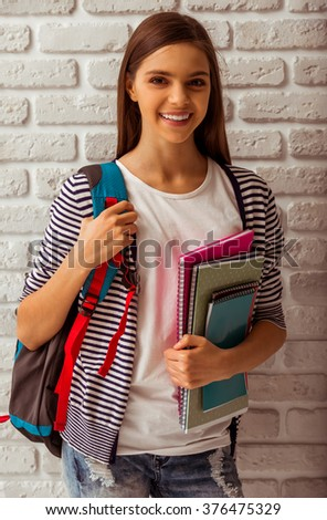 Cute teenage girl in casual clothes standing with a school backpack and books against white brick wall, looking in camera and smiling