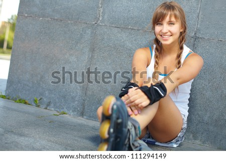 Cute teenage girl in roller skaters looking at camera - stock photo