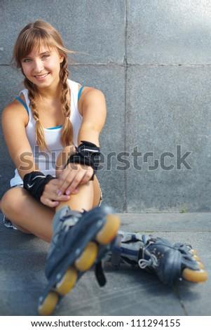 Cute teenage girl in roller skaters looking at camera - stock photo