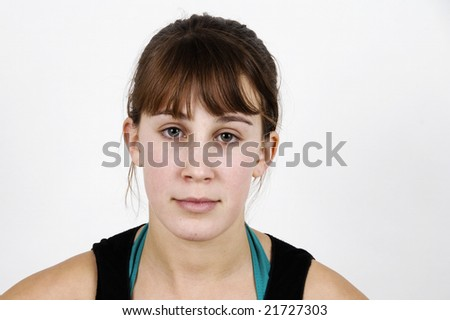 Cute teenage girl, looking straight at the viewer, against a white background in a studio. - stock photo