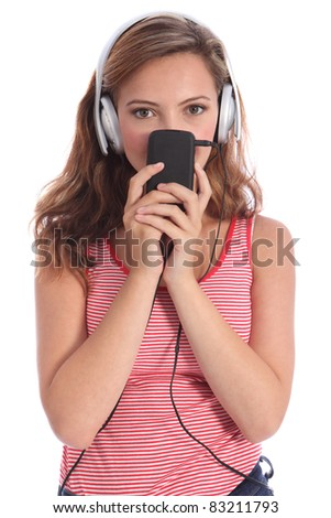 Cute teenage girl peeping over mobile phone listening to music with silver headphones. She is wearing a colourful red and white vest and has long brown blonde hair. - stock photo