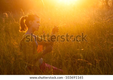 Cute teenage girl picking flowers on the meadow on sunny spring day. - stock photo