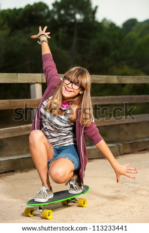 Cute teenage girl practicing on skateboard outdoors. - stock photo