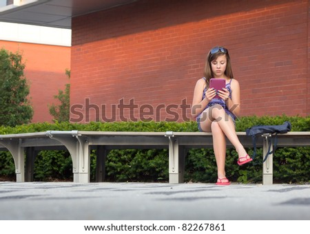 Cute teenage girl reading from a digital device book on a bench outside a school - stock photo