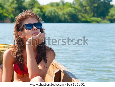 Cute teenage girl sunbathing on the boat on sunny summer day.