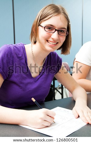 Cute teenage girl taking a standardized test in high school. - stock photo