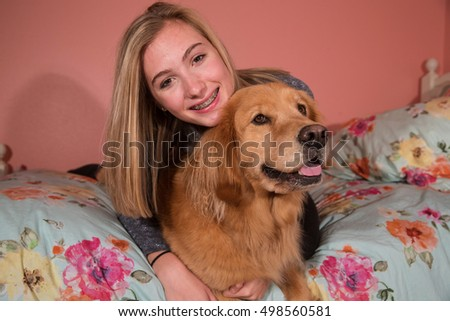 Cute teenage girl with braces and her golden retriever dog