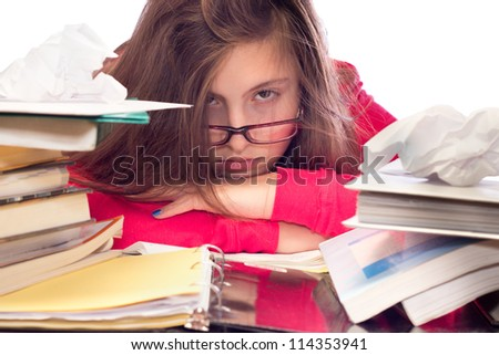 Cute teenage girl with glasses, surrounded by books and school work, looking frustrated - stock photo