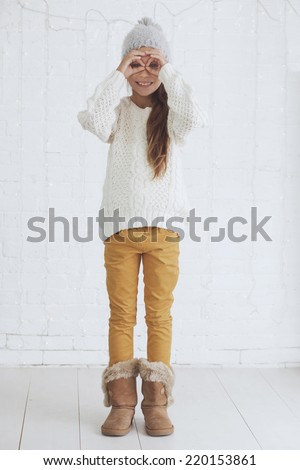 Cute teenage girl 8-9 years old wearing knit trendy winter clothes posing over white brick wall - stock photo