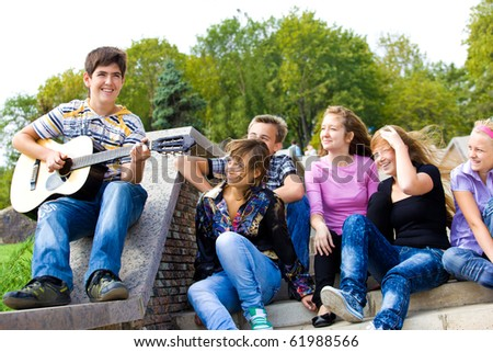 Cute teenage guy playing guitar for his friends - stock photo
