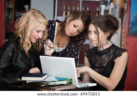 Cute teenaged girls distracted with a laptop while doing homework in a cafe