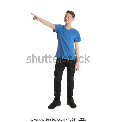 Cute teenager boy in blue T-shirt standing and poinitng up side over white isolated background full body