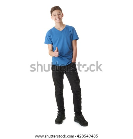 Cute teenager boy in blue T-shirt standing and pointing forward over white isolated background full body - stock photo