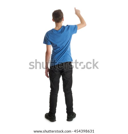 Cute teenager boy in blue T-shirt standing and pushing button over white isolated background full body from back