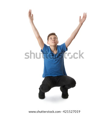 Cute teenager boy in blue T-shirt with stretching hands up sitting over white isolated background full body