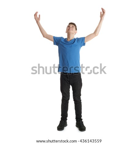 Cute teenager boy in blue T-shirt with stretching hands up standing over white isolated background full body