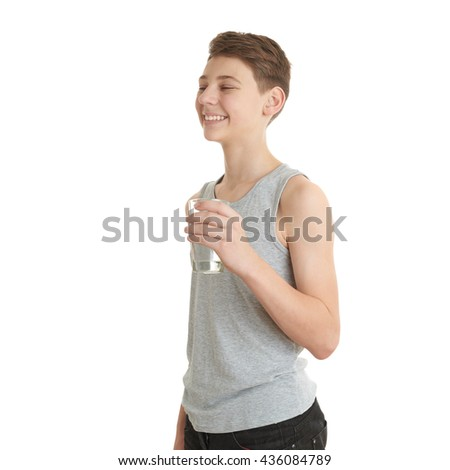 Cute teenager boy in gray shirt with glass of water over white isolated background, half body - stock photo