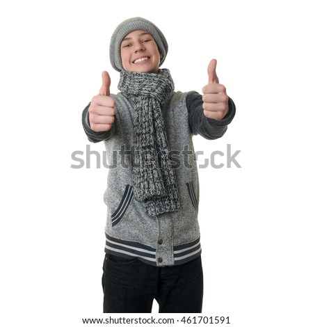 Cute teenager boy in gray sweater, hat and scarf showing thumb up sign over white isolated background, half body