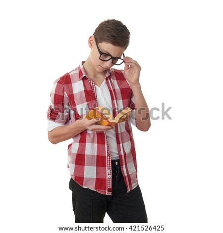 Cute teenager boy in red checkered shirt, glasses and a book over white isolated background, half body, reading concept