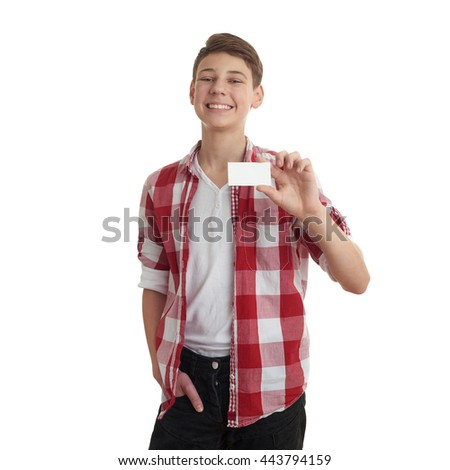 Cute teenager boy in red checkered shirt with small paper card over white isolated background, half body - stock photo