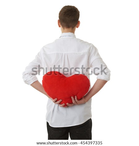 Cute teenager boy in white shirt holding with red plush heart from back over white isolated background, half body - stock photo