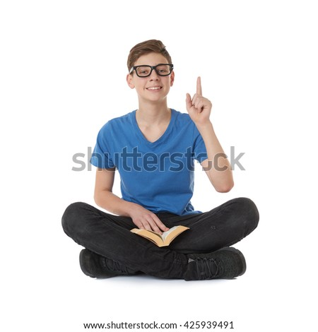 Cute teenager boy poinitng up with book in blue T-shirt, glasses and lotus posture over white isolated background - stock photo