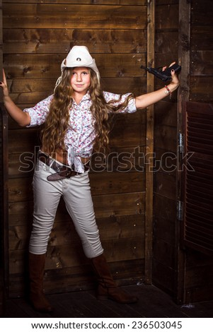 Cute teenager girl in a cowboy hat on a ranch posing with toy gun - stock photo
