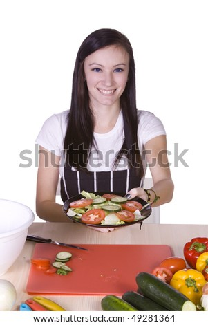 Cute Teenager in the Kitchen Handing a Plate of Salad - stock photo