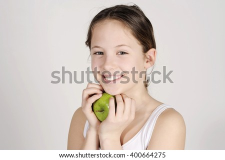cute teenager with apple, healthy eating and food concept- happy girl holding green apple studio shot - stock photo