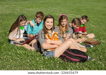 Cute teenagers sitting together studying outdoors