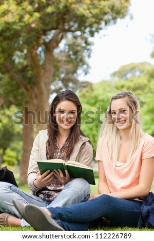 Cute teenagers sitting while studying with a textbook in a park - stock photo