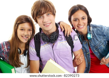 Cute teens with headphones smiling at camera - stock photo