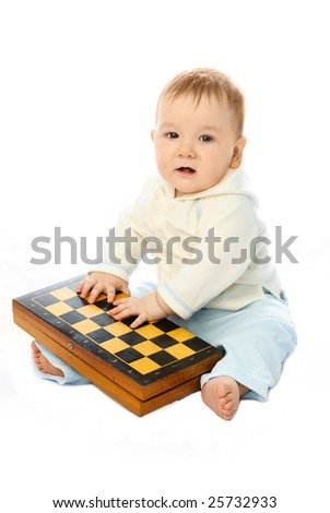 cute ten months old baby sitting on the floor with a chessboard in his hands - stock photo