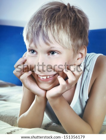 Cute tender blond boy wearing a blue undershirt smiles happily having a rest on a sofa watching TV    - stock photo