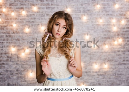 Cute tender slim girl with blond curly hair standing in a studio with white background with flashlights. She has two ribbons in her hair and looks innocent. - stock photo