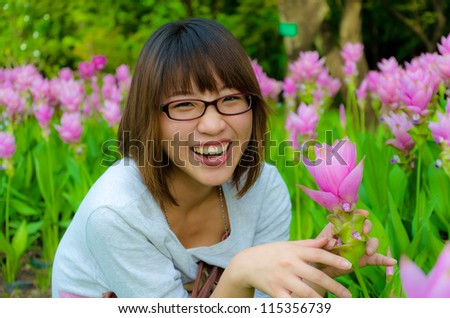 Cute Thai girl are very happy with flowers (Siam Tulip). She is laughing with joy. - stock photo
