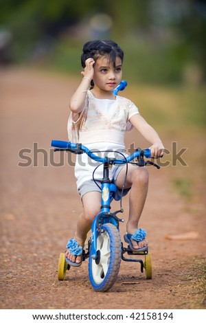 cute thai-indian girl riding her bike on a dirtroad - stock photo