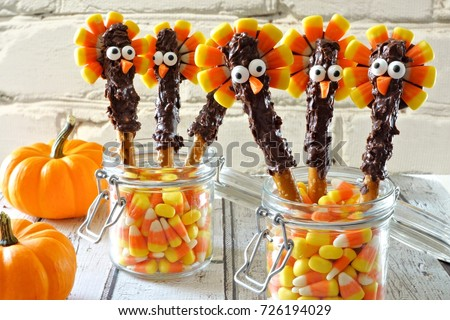 Cute Thanksgiving turkey pretzel sticks with candy corn, still life against a white brick background