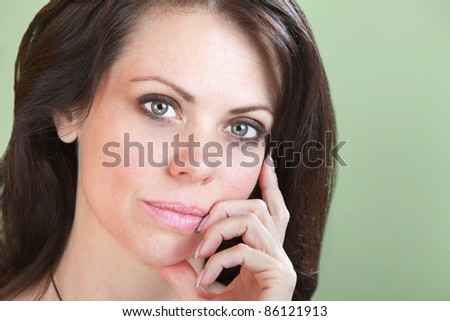 Cute thinking young woman on green background with fingers to chin - stock photo