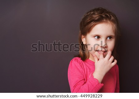 Cute thoughtful little girl with her finger in her mouth staring pensively off to the side of the frame against a dark background with copy space - stock photo