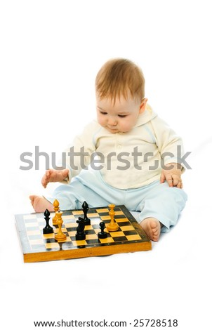 cute thoughtful ten months old baby playing chess on the floor - stock photo
