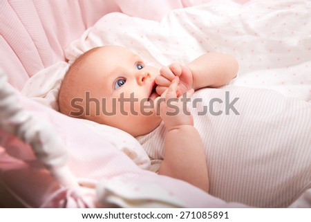 Cute three month baby girl laying in a bassinette looking side - stock photo