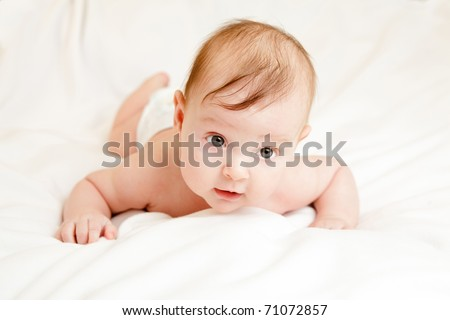 Cute three months old caucasian baby girl on white blanket. - stock photo