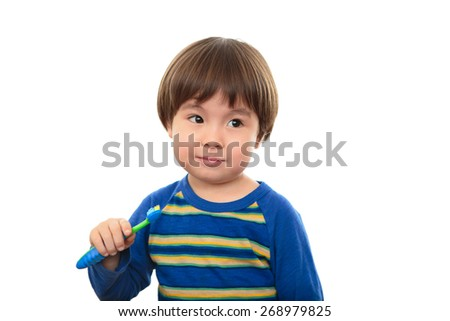 Cute three year old boy holding toothbrush, unsure if he wants to brush his teeth, isolated on white background. Two year old child dental health concept, looking to the side. Half Asian boy, Japanese - stock photo