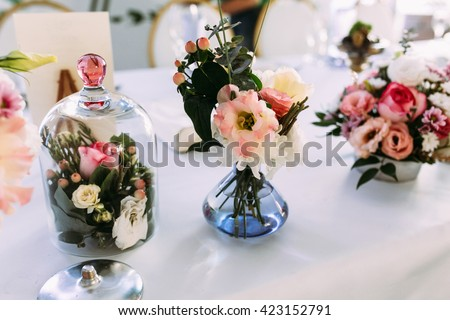 Cute tiny bouquet of the pink flowers on the table - stock photo