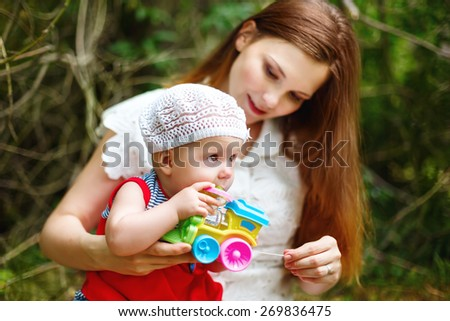 Cute Toddler Baby Girl sitting on Mom`s Hands, playing with Toy. Relaxing in green summer Park. Selective focus on baby`s eyes. Grain added for best impression. - stock photo