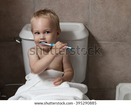 Cute toddler boy brushing his teeth after having a bath. Boy after evening before sleep rituals.