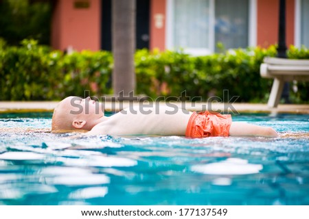 Cute toddler boy closed his eyes and relaxing in swimming pool  - stock photo