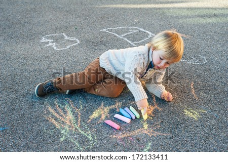 Cute toddler boy drawing with chalk on a nice day outdoors - stock photo